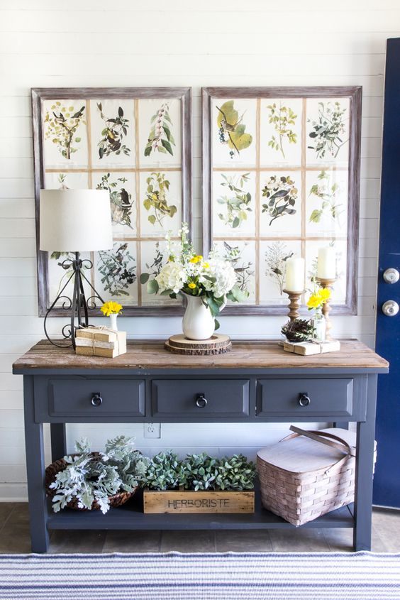 a farmhouse console table with a wooden countertop, much greenery in baskets and boxes, vintage botanical posters