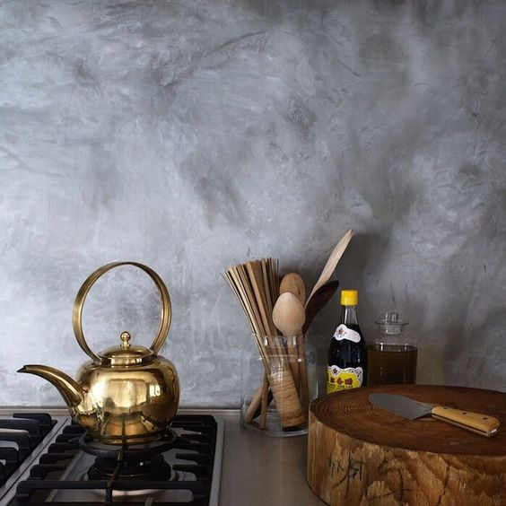 a grey plaster backsplash, brass and wood create a fantastic ambience in the kitchen