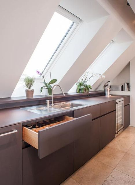 a minimalist grey kitchen with a couple of skylights plus additional light