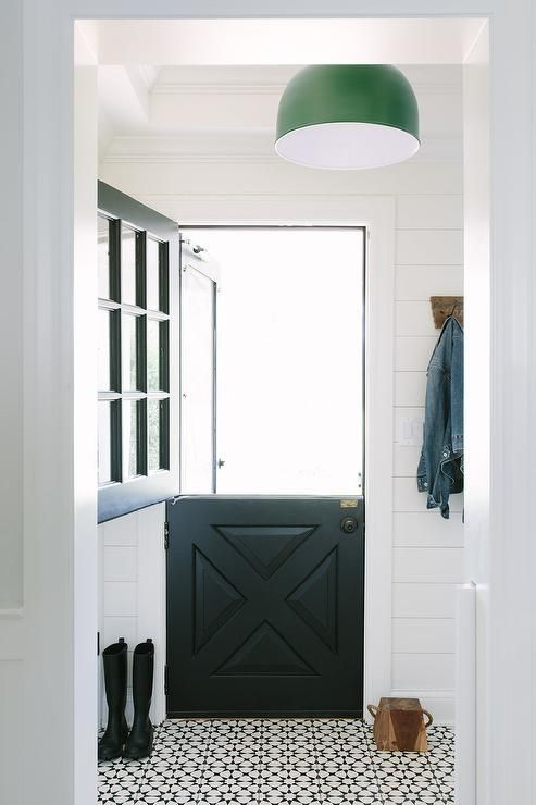 A Modern Farmhouse Entryway With Black Dutch Door And Mosaic White Floor
