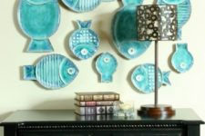 19 a whimsical gallery wall made of turquoise fish-shaped decorative plates is a cute idea