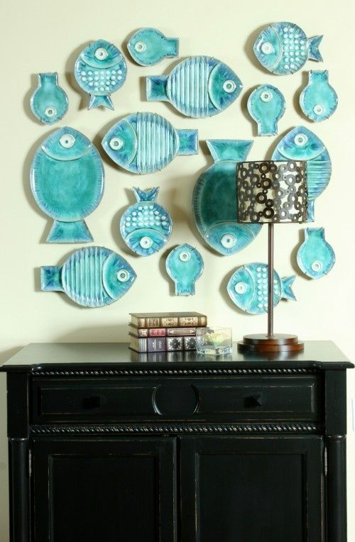 a whimsical gallery wall made of turquoise fish-shaped decorative plates is a cute idea