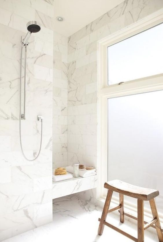 white marble tiles, frosted glass windows and a wooden stoll create a welcoming bathing space