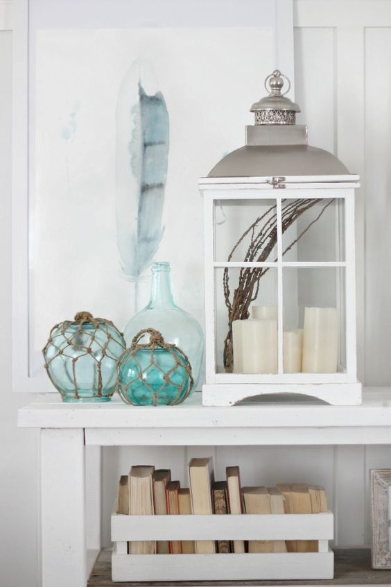 a beachy console with an oversized lantern with candles, floats, a feather artwork and a crate with books
