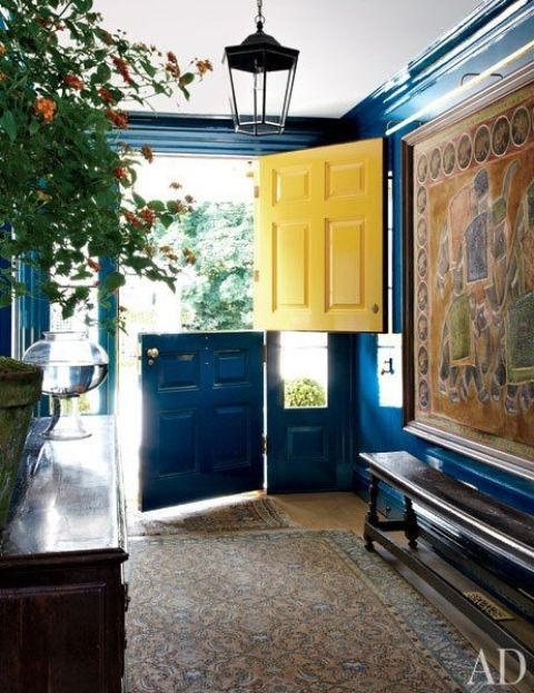 a bold entryway with a bright blue and yellow Dutch door that makes a colorful statement