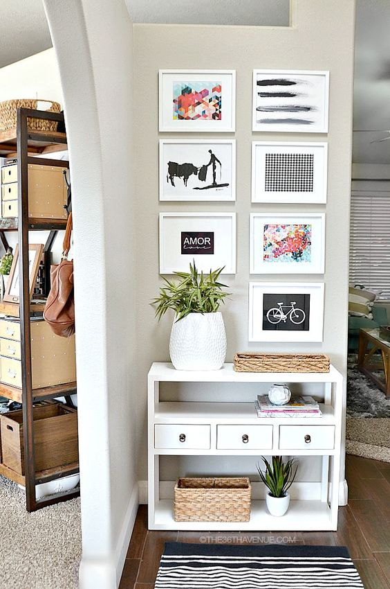 a small console with bold artworks over it, potted greenery and some baskets for storage