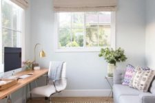 20 a small yet clean home office with a wooden trestle leg desk by the window and a grey sofa that can become a bed