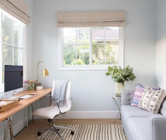 a small yet clean home office with a wooden trestle leg desk by the window and a grey sofa that can become a bed