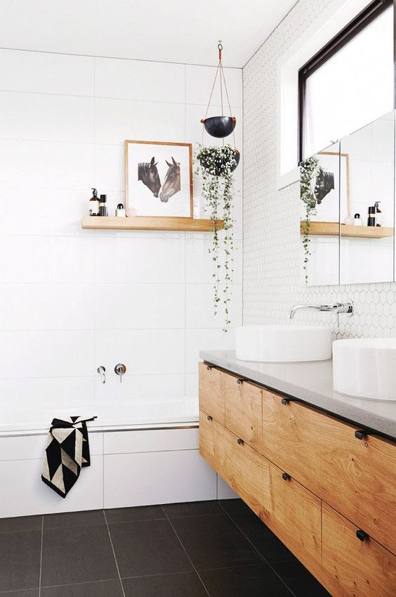 a white bathroom space is spruced up with a black floor and a wooden shelf and vanity