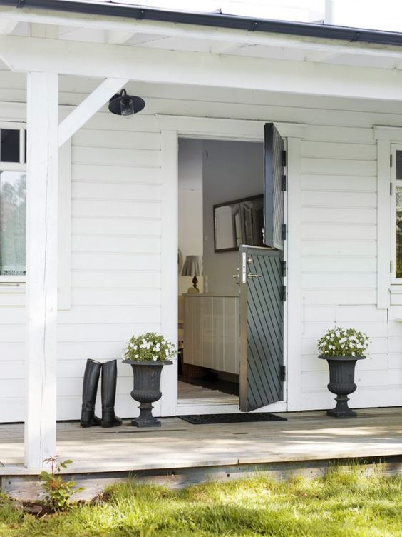 a black striped Dutch door is a bold contrasting touch for a white house
