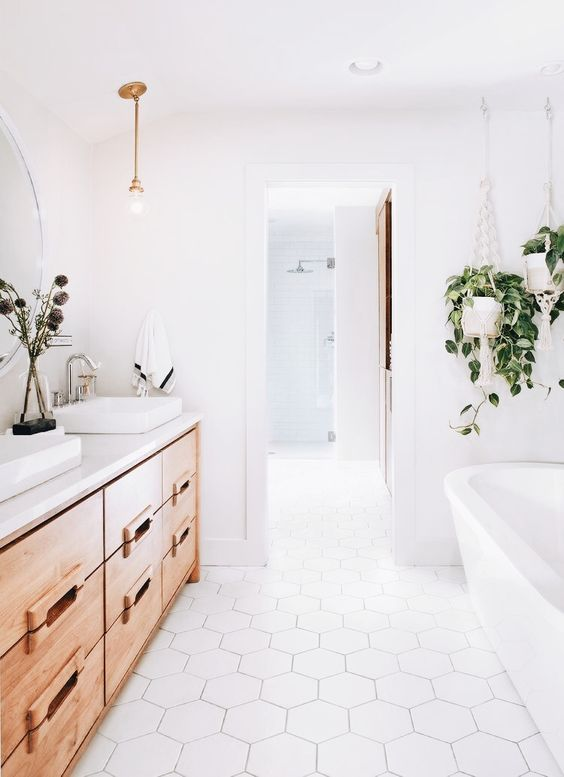 a clean white space with a large light-colored wood vanity and some potted greenery