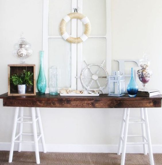 a console table with colored bottles, greenery, a lantern and some shells in jars for a seaside feel
