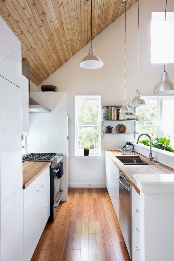 a double height narrow kitchen with many windows that flood the space with light, and wooden touches for coziness