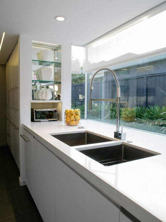 a glossy white kitchen is connected to the private courtyard through a large window