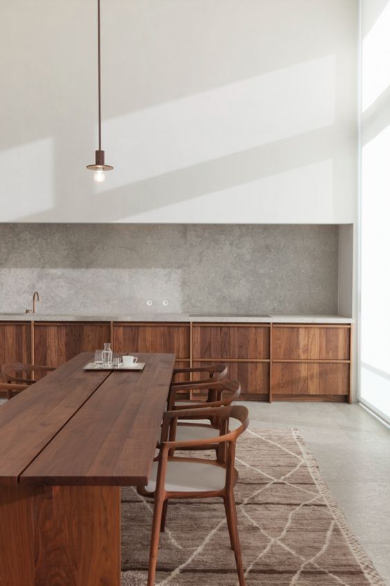 a minimalist kitchen with a grey plaster backsplash that adds color and texture to the space