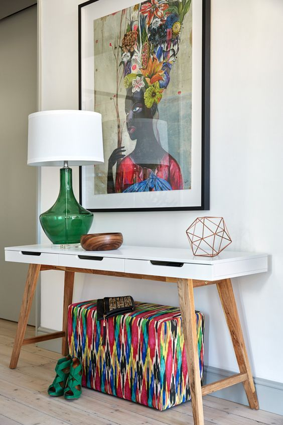 a super colorful artwork, a bright upholstered ottoman and a green lamp for summer