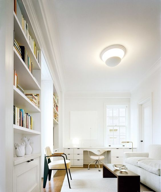 a very elegant space with a convertible sofa, bookcases and a large desk by the window