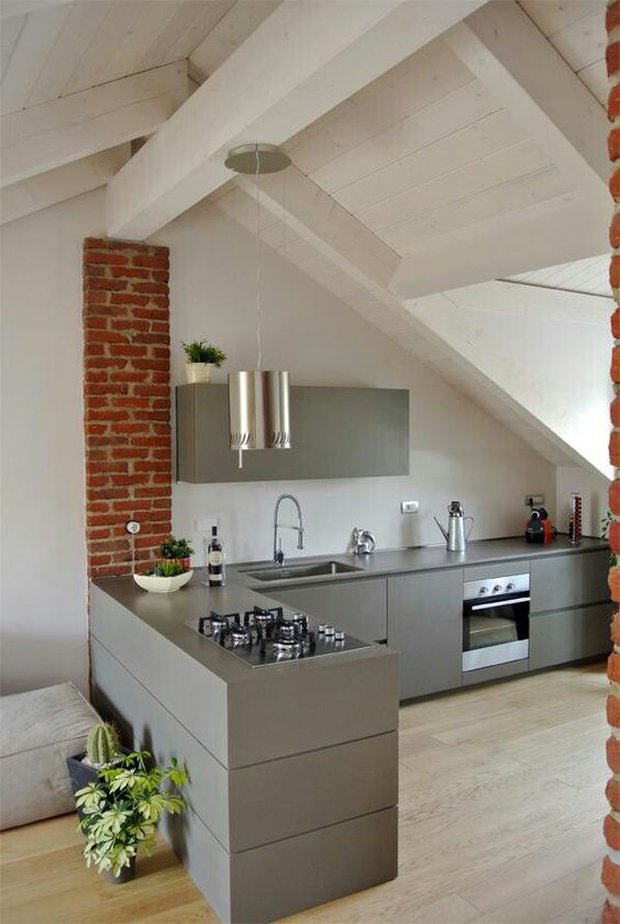 a minimalist kitchen with skylights and brick touches plus a pendant lamp to highlight the ceiling height