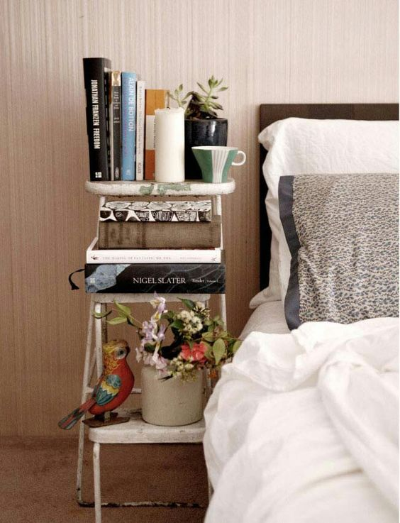 a small vintage ladder acts as a bedside bookshelf and doesn't cost a lot of money