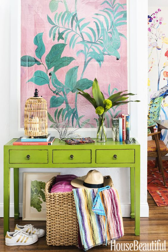 a super colorful console with a birdcage candle holder, greenery, a bold artwork and a basket with colorful textiles