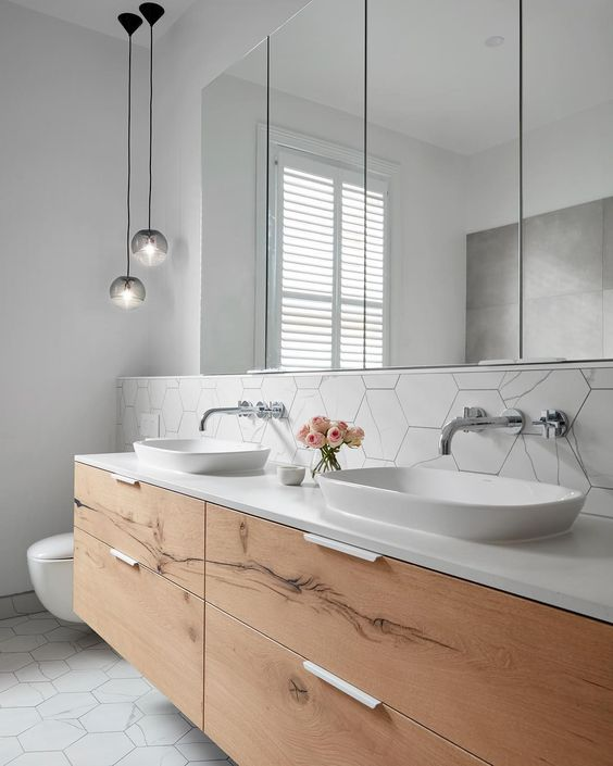 a white bathroom with a minimalist wooden vanity plus white sinks