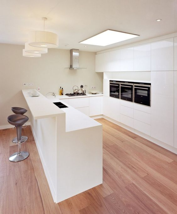 a kitchen island with a raised bar part can be used for both having breakfast and drinks
