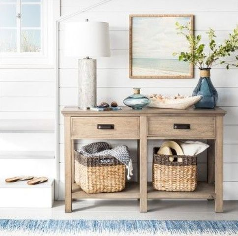 a rustic beachy console, baskets under it, a wooden bowl with shells and some colored glass plus an artwork