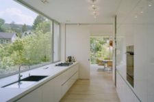 23 a serene white minimalist ktichen with a panoramic window to enjoy the views