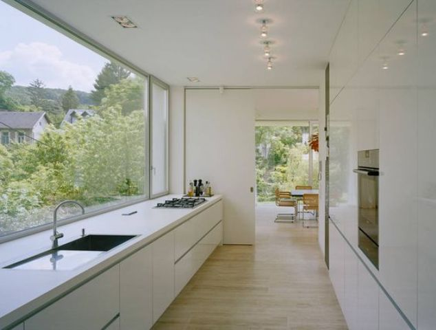 a serene white minimalist ktichen with a panoramic window to enjoy the views