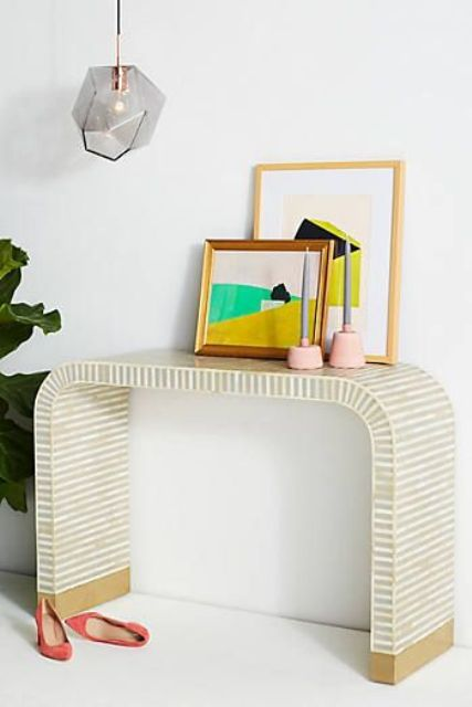 a waterfall inlay console, colorful artworks and candle holders for a mid-century modenr interior