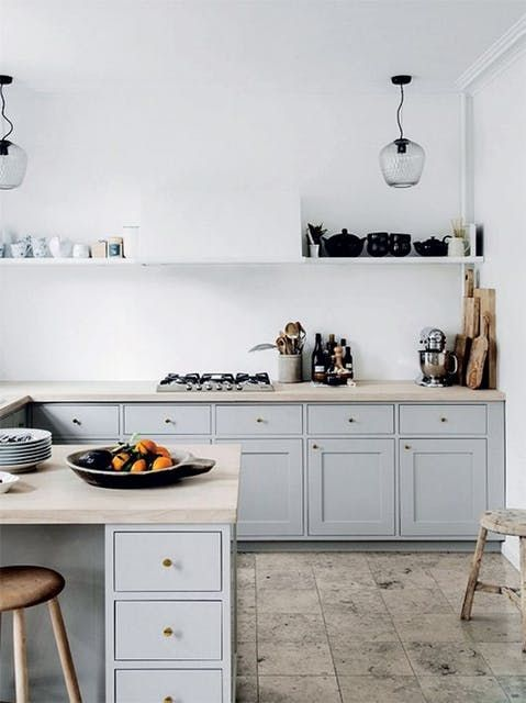 a white plaster wall and backsplash plus light grey cabinets for a serene kitchen look