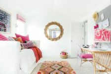23 an adorably colorful guest bedroom with a convertible sofa and a wicker desk plus a pink chair