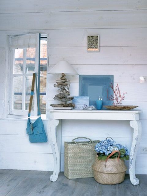 a small console with corals, a driftwood lamp, an abstract artwork and baskets under the table