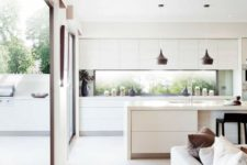 24 a white contemporary kitchen with a window backsplash and glazed walls to tie the spaces