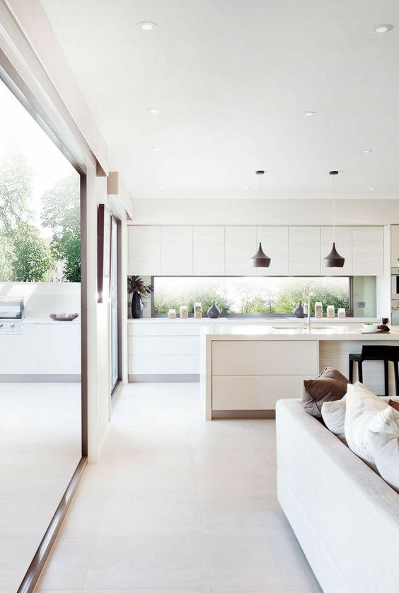 a white contemporary kitchen with a window backsplash and glazed walls to tie the spaces