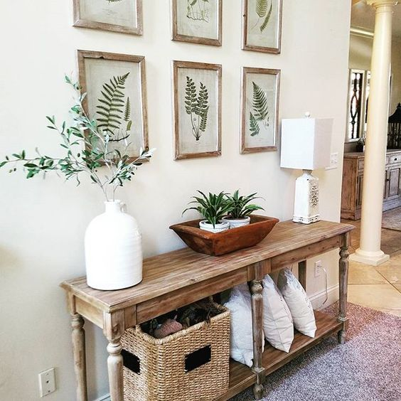 a wooden console, botanical artworks, potted greenery and a basket for storage for summer