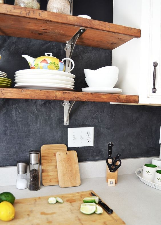 black plaster backsplash, white cabinets and wooden shelves for a bright modern look