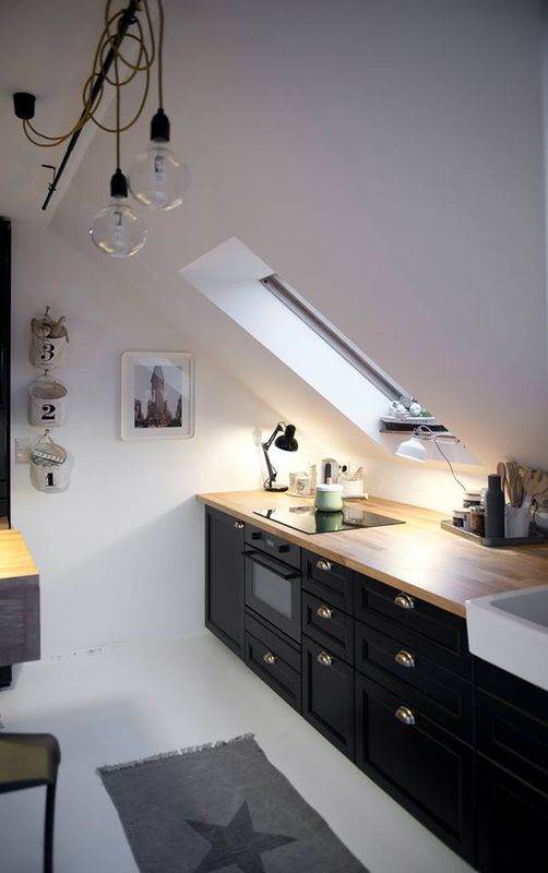 a Scandinavian attic kitchen with black cabinets, wooden countertops and skylights