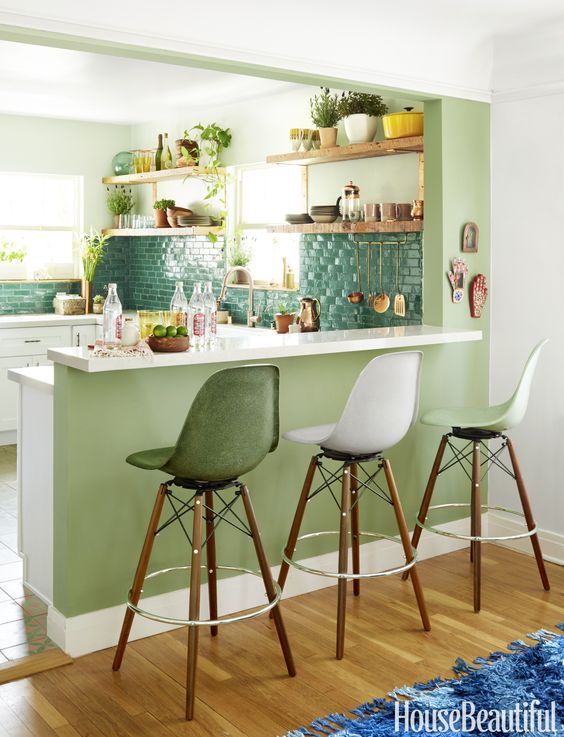 a raised up breakfast bar is attached to a kitchen island and tall stools are comfy for sitting