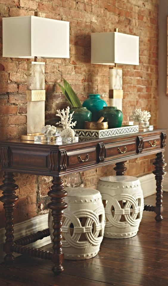 a vintage console table with corals, colored pots and vases and stone base lamps