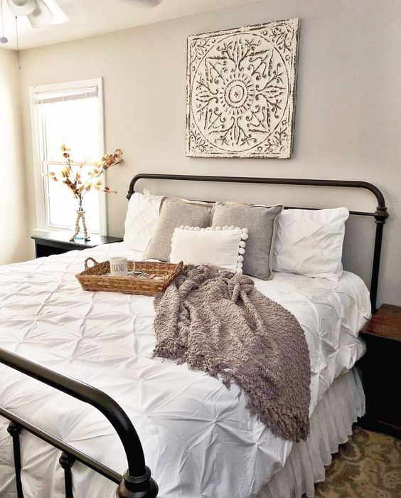 a cozy farmhouse style guest bedroom with an artwork and some baskets