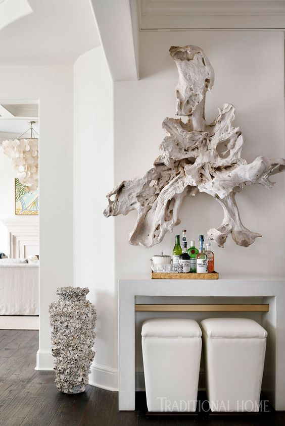 a large whitewashed piece of driftwood is a unique wall art idea for a coastal home