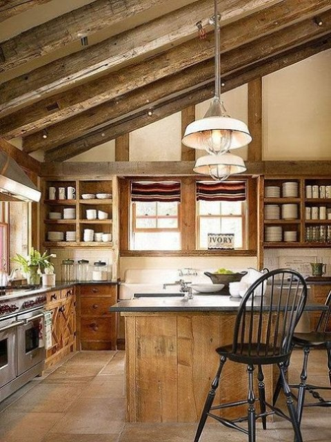 a rustic countryside kitchen with wooden beams and open storage plus pendant lamps and windows for much light