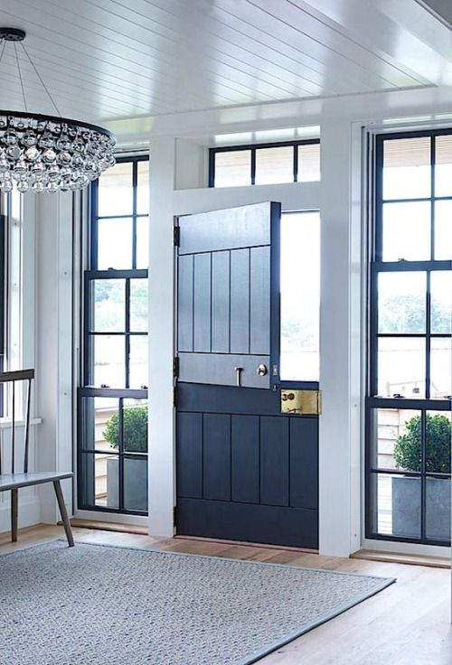 a stylish contemporary entryway with a navy Dutch door and windows on both sides
