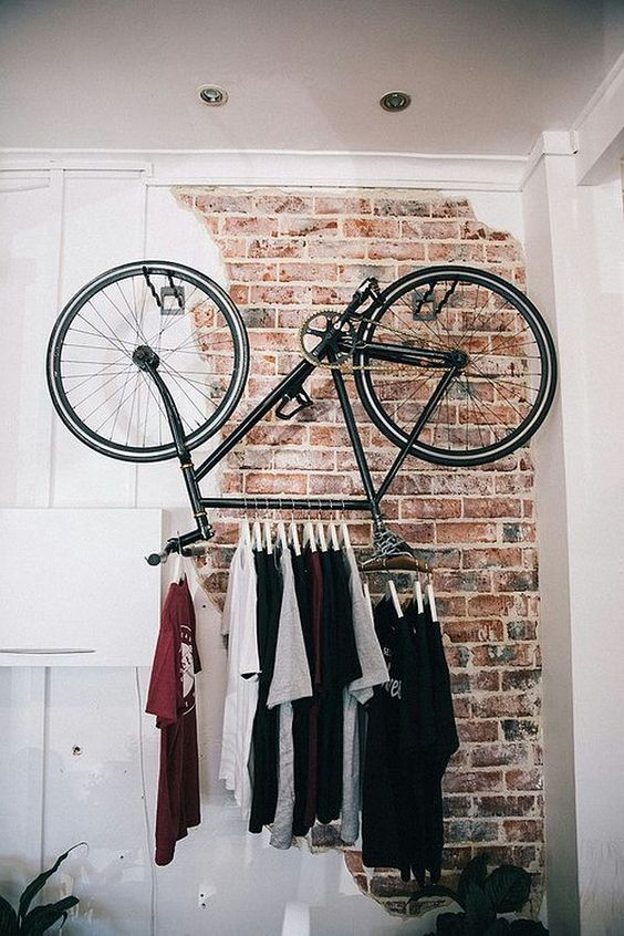 a super cool t-shirt rack made of a bicycle for an edgy touch to your interior