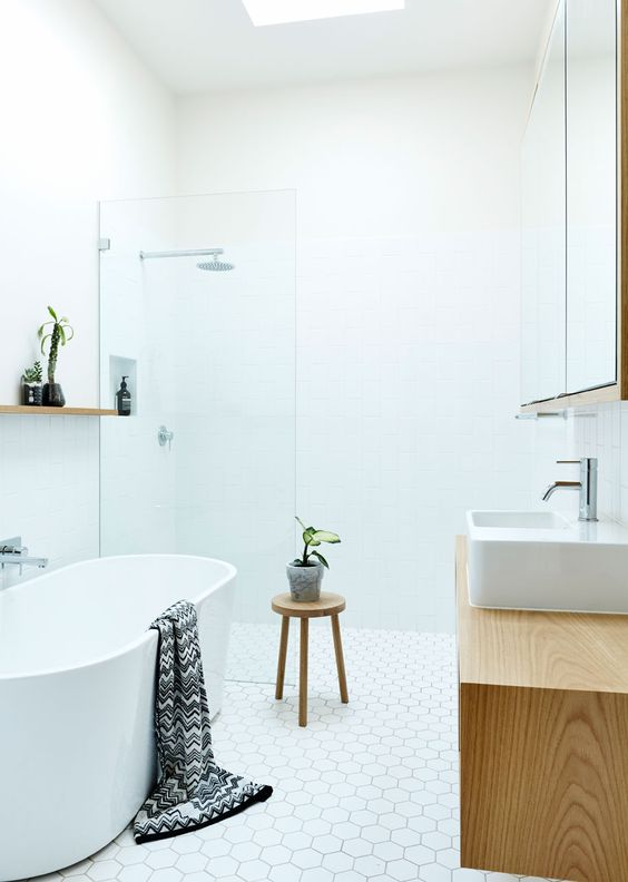 a white bathroom with a wooden vanity and stool for a textural touch