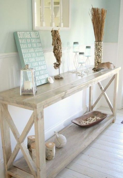 a whitewashed console table, candles in glass candle holders, starfish, a sea horse of driftwood and a shell clad vase