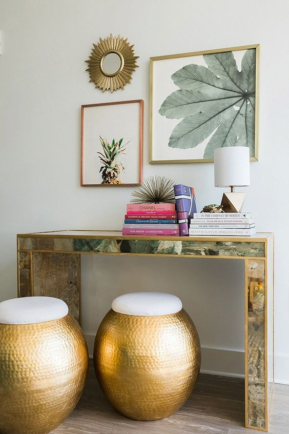 an encrusted console table, colorful books, tropical artworks over the table and hammered metal ottomans