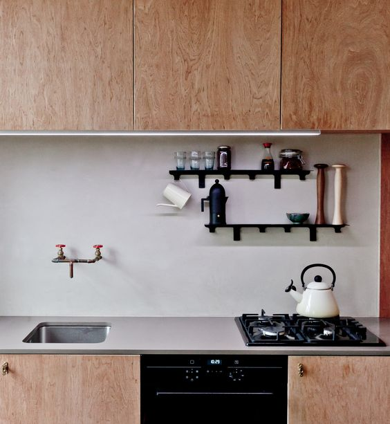 light-colored plywood cabinets and a blush plaster backsplash for a unique mid-century modern look