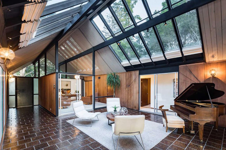 This mid century modern house features a lot of skylights and spaces separated with glass dividers